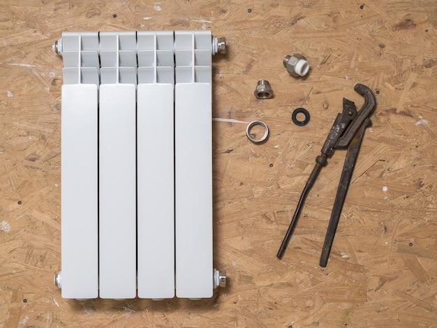 Radiador quebrado e ferramentas de reparo no piso de madeira. acidente do sistema de aquecimento de uma casa privada. radiador de aquecimento.