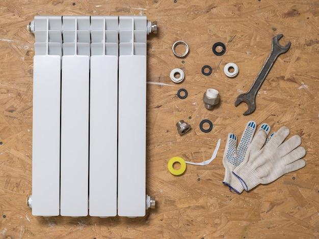 Radiador quebrado e material de reparo no piso de madeira. acidente do sistema de aquecimento de uma casa privada. radiador de aquecimento.