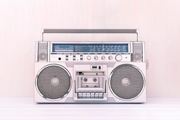 Rádio cassete retrô dos anos 80 na cor prata com fundo de madeira clara. toca o conceito de música.