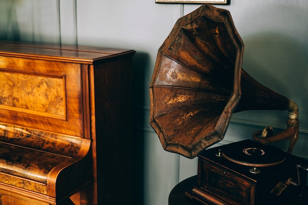 Rádio gramofone antigo retrô com alto-falante de corneta fica com piano velho