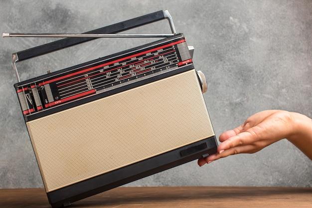 Rádio retrô com antena na mão