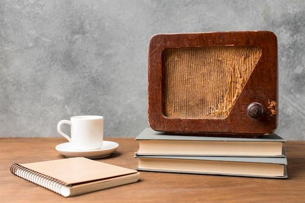 Rádio vintage de vista frontal em uma pilha de livros e café