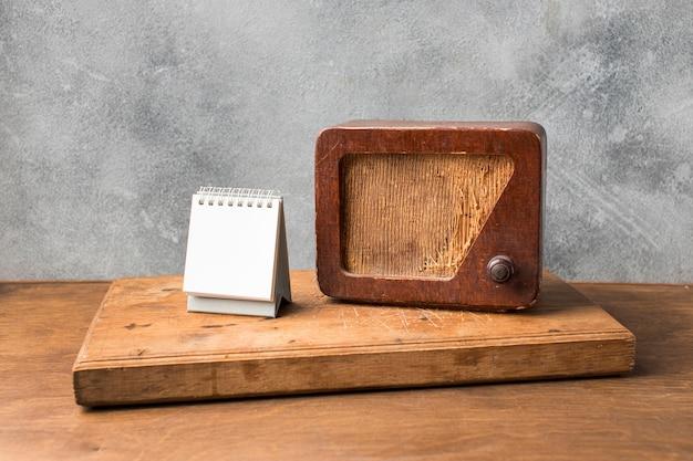 Rádio vintage e calendário branco na placa de madeira