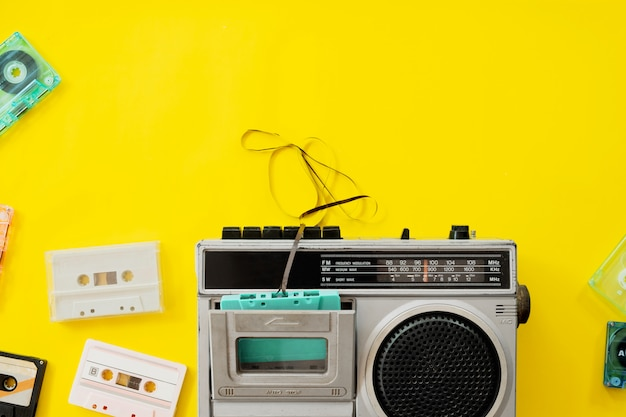 Rádio vintage e toca-fitas em fundo amarelo