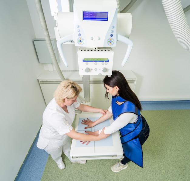 Radiologista e paciente em uma sala de raio-x. raio-x da mão humana. sistema clássico de raio-x montado no teto.