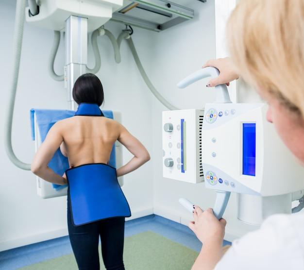 Radiologista e paciente em uma sala de raio-x. sistema clássico de raio-x montado no teto.