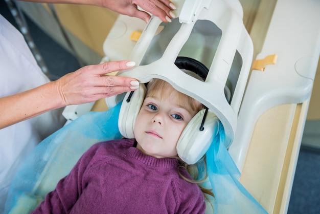 Radiologista prepara a menina para um exame de ressonância magnética do cérebro