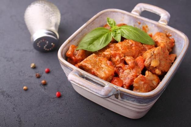 Ragout de carne com cebola, cenoura e tomate, decorado com manjericão,
