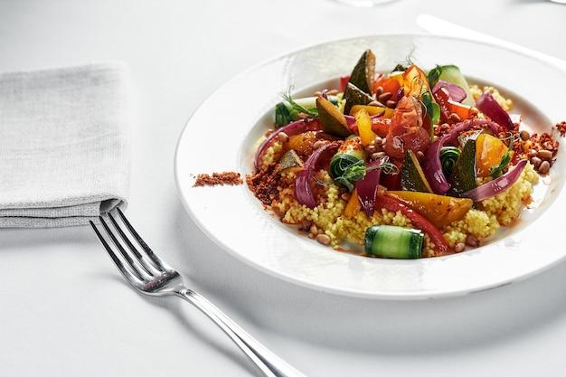 Ragu de legumes com abobrinha, repolho, batata, tomate e pimentão em molho cremoso no prato, uma toalha, salsa e um garfo no fundo de uma placa de madeira leve