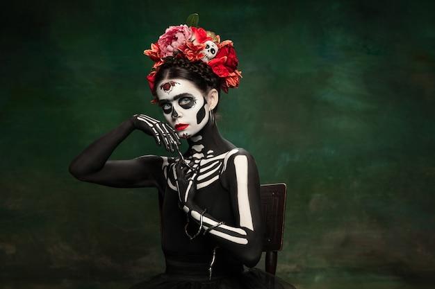 Rainha cobra. jovem como a morte de santa muerte ou caveira de açúcar com maquiagem brilhante. retrato isolado em fundo verde escuro do estúdio com copyspace. comemorando o dia das bruxas ou o dia dos mortos.