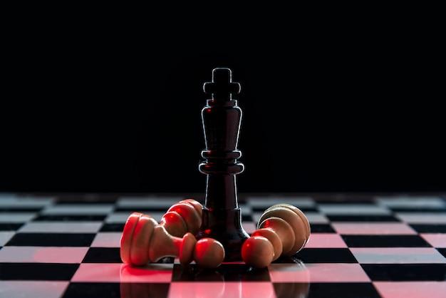 Rainha do xadrez derrota um lote de peões brancos em um tabuleiro de xadrez