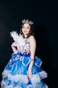Rainha em um vestido azul com um leque em um fundo preto