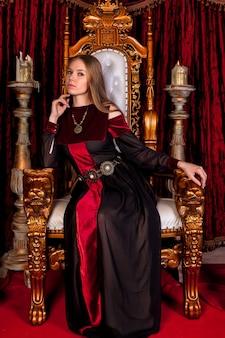 Rainha medieval em trajes históricos no trono dourado do castelo. retrato de jovem em um vestido de estilo antigo em um trono antigo na sala de recepção da fortaleza. conceito de eventos temáticos de fantasias