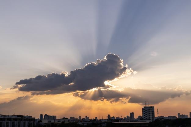 Raio de sol através da nuvem dramática durante a hora do pôr do sol, com construção de silhueta abaixo