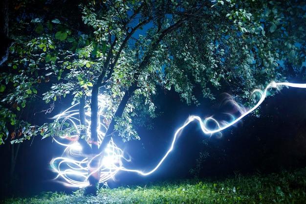 Raio. relâmpagos ramificados em azul e magenta que atingem uma árvore à noite durante uma tempestade de verão