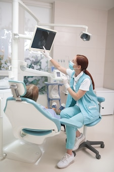 Raio-x na tela. dentista infantil ruivo usando máscara e uniforme mostrando o raio-x para uma menina