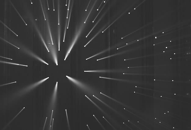 Raios de luz através de pequenos buracos em um espaço escuro