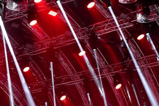 Raios de luz de iluminação de concerto em um fundo escuro acima da tela do projetor.