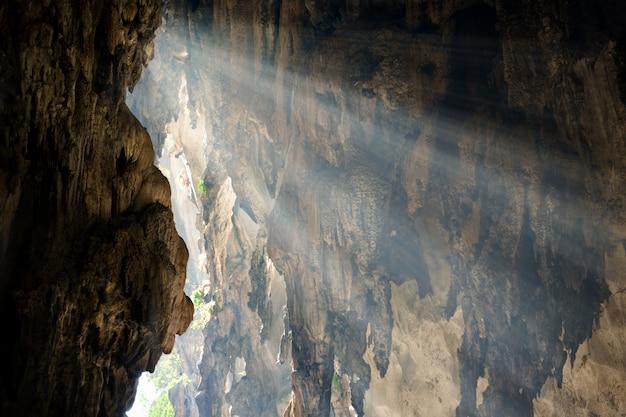 Raios de luz solar caem na parede da caverna. conceito de esperança, descoberta.
