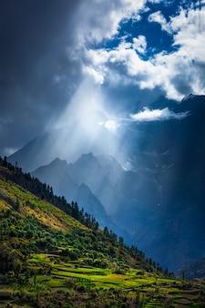 Raios de sol através das nuvens no vale do himalaia no himalaia