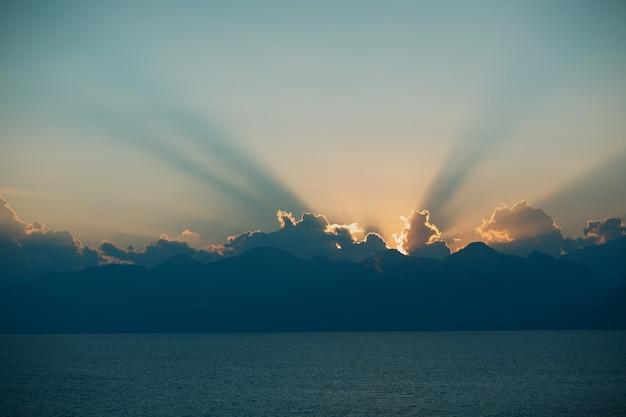 Raios do pôr do sol dramáticos no céu nublado e escuro sobre o oceano