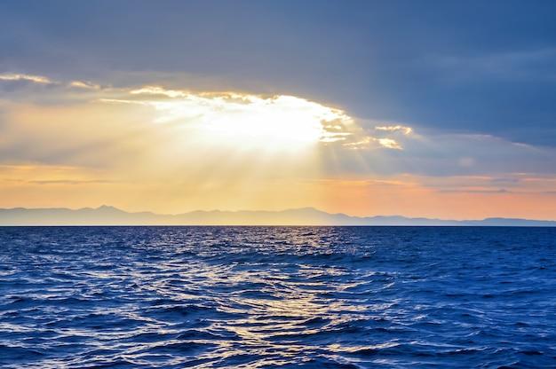 Raios do sol brilhando através das nuvens mar adriático, montenegro, europa.
