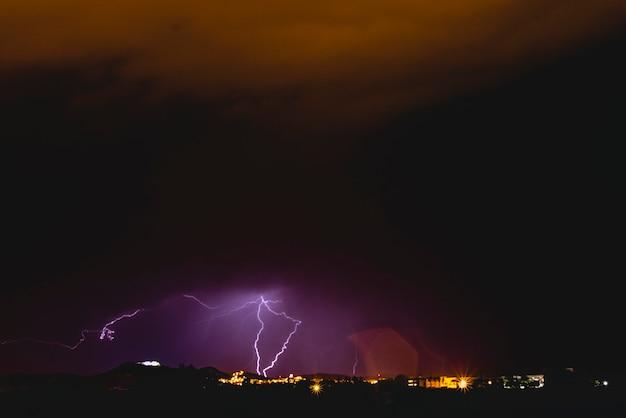 Raios em uma tempestade de noite com luz e nuvens.
