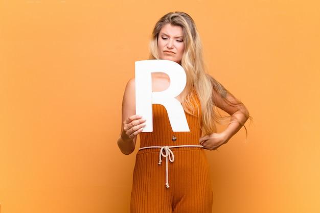 Raiva, raiva, desacordo, segurando a letra r do alfabeto para formar uma palavra ou frase.