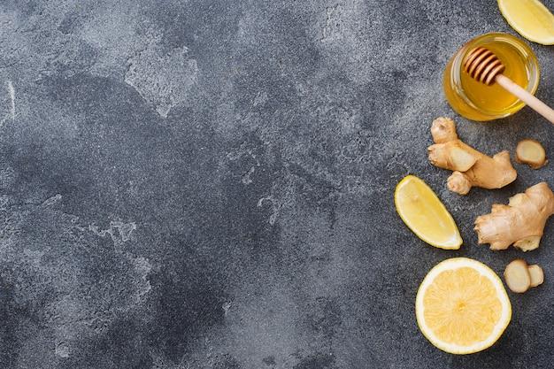 Raiz de gengibre e mel de limão na superfície cinza escura