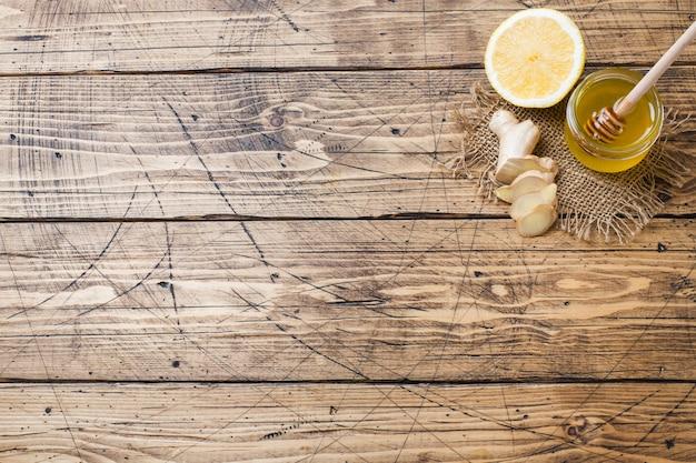Raiz de gengibre e mel de limão na superfície de madeira