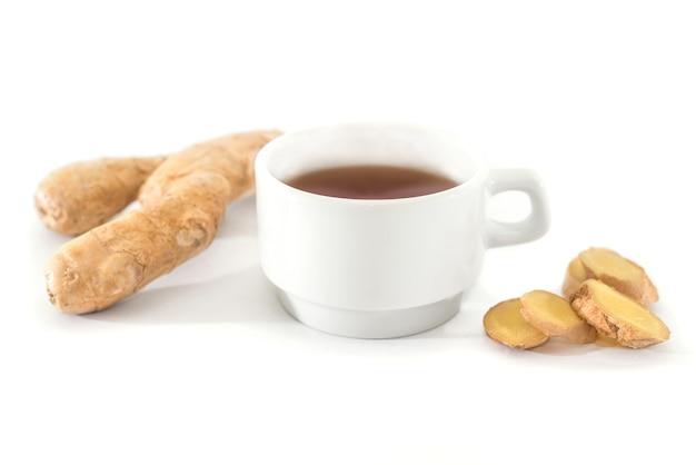 Raiz de gengibre fresco, xícara de chá isolada na mesa branca, especiarias saudáveis, chá de gengibre