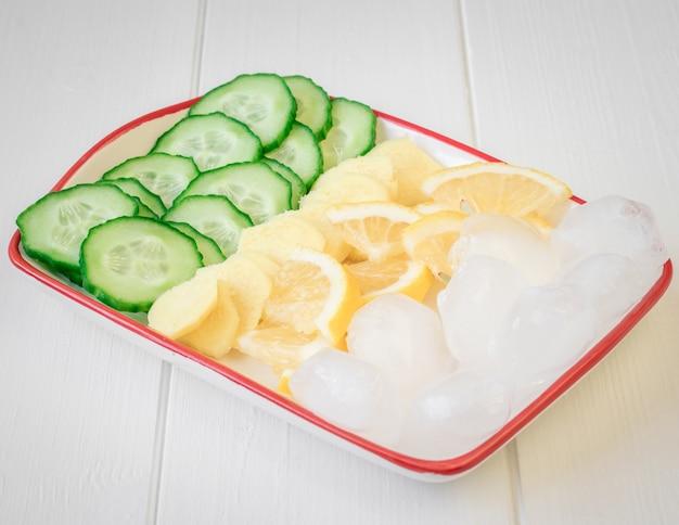 Raiz de gengibre, limão, pepino, gelo em uma mesa de madeira branca.
