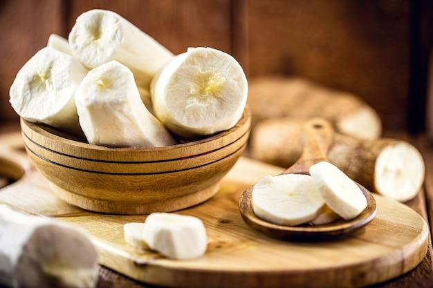 Raiz de mandioca descascada, ingrediente culinário, em fundo de madeira