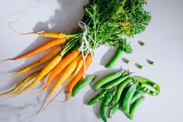 Raízes frescas sujas legumes cenouras e ervilhas em fundo de mármore