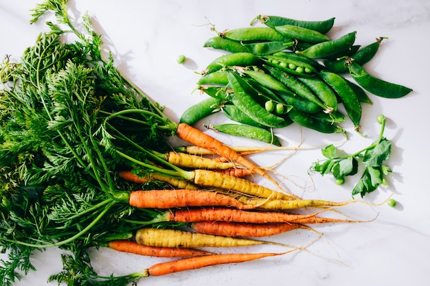 Raízes frescas sujas legumes cenouras e ervilhas no fundo de mármore, vista plana leigo, superior