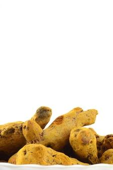 Raízes ou cascas de cúrcuma secas isoladas na superfície branca
