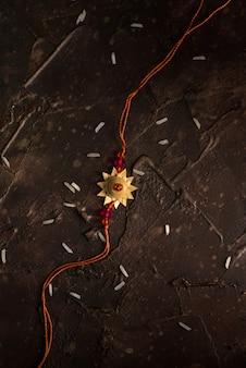 Raksha bandhan com um elegante rakhi e arroz espalhado. pulseira tradicional indiana, símbolo de amor entre irmãos e irmãs.