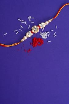 Raksha bandhan: rakhi com grãos de arroz e kumkum. um festivo indiano. pulseira indiana tradicional, que é um símbolo de amor entre irmãos e irmãs.