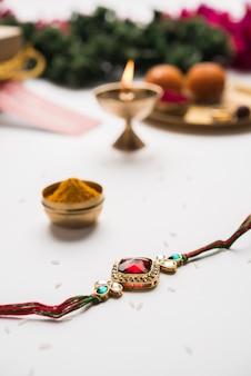 Raksha bandhan / rakshabandhan rakhi com arroz haldi kumkum, doce mithai, caixa de presente, foco seletivo
