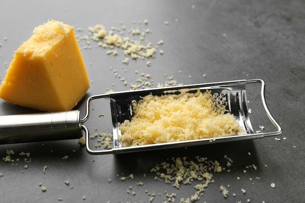 Ralador de metal e queijo em fundo escuro
