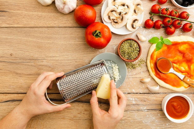 Ralar queijo com outros ingredientes da pizza