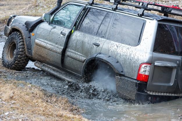 Rally em suvs russos na lama no inverno veículo todo terreno preso foi puxado para fora do rio