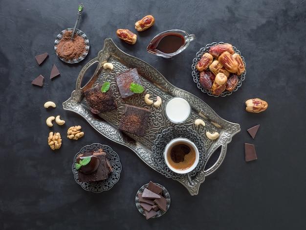 Ramadan festivo. brownies com tâmaras, leite e café são dispostos em uma superfície preta.