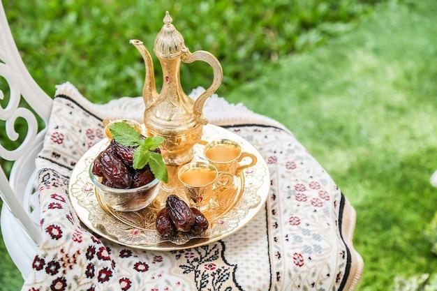 Ramadan inspiração mostrando as palmas de data em uma tigela com o jogo de chá dourado