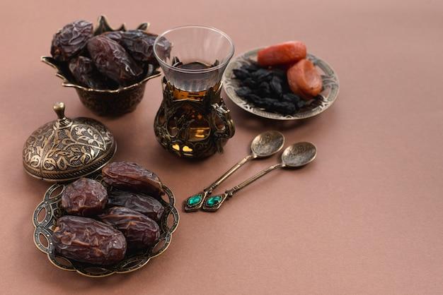 Ramadan kareem com copo de chá; datas premium e frutos secos árabes no fundo marrom