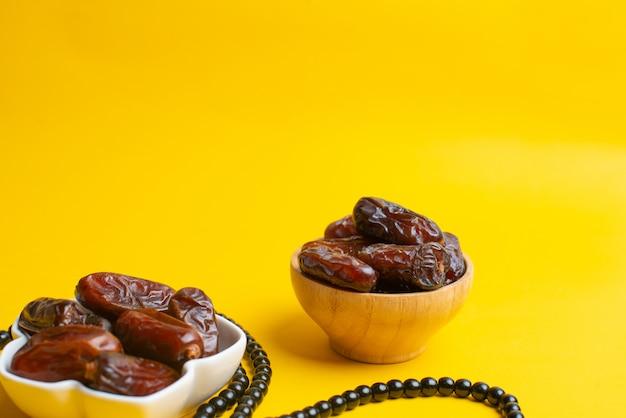 Ramadan kareem festival, datas na tigela com rosário em fundo amarelo