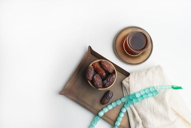 Ramadan kareem festival, datas na tigela de madeira com uma xícara de chá preto e rosário