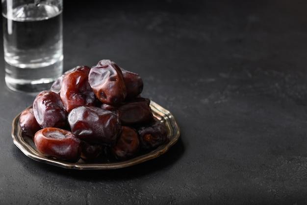 Ramadan kareem. iftar começa com um copo de água e as datas. fechar-se.