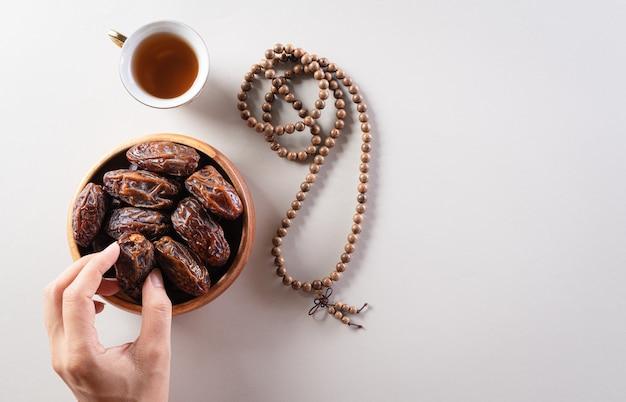 Ramadan kareem, mãos pegando frutas tâmaras, chá e contas do rosário.