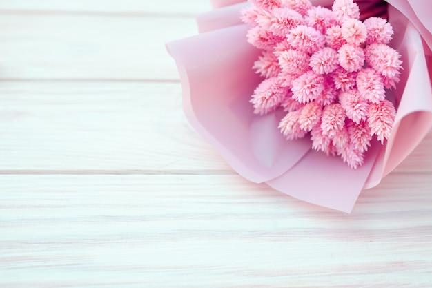 Ramalhete bonito de flores cor-de-rosa secas em um fundo branco de madeira.
